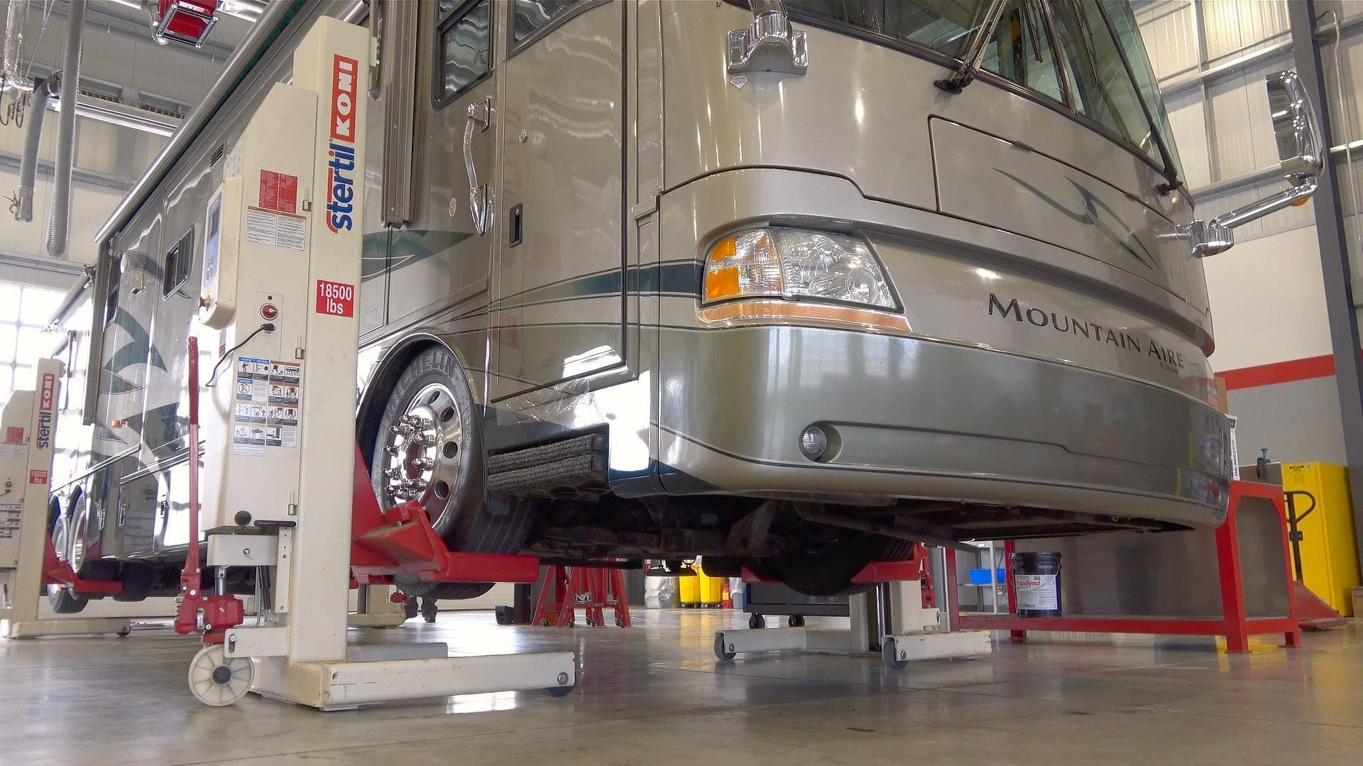 A motorhome on lifts while at an RV mechanic